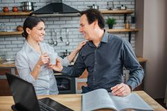 O homem e a mulher alegres estão junto na cozinha Sorriem entre si Mulher para dar o copo branco para equipar Toca no seu imagens de stock royalty free