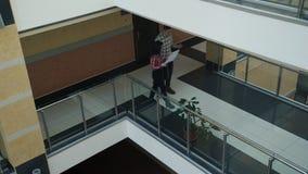 O homem e a mulher andam ao longo do salão da universidade ou do centro de negócios que guardam originais filme