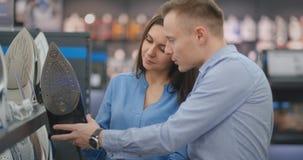 O homem e a mulher bonitos dos pares da família escolhem o ferro novo na loja dos produtos eletrónicos de consumo vídeos de arquivo