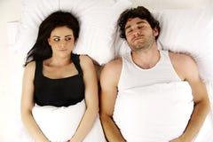 O homem e a mulher colocaram em uma cama branca Fotos de Stock Royalty Free