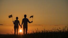 O homem e a mulher com as bandeiras americanas em suas mãos estão olhando o sol de aumentação fotografia de stock royalty free