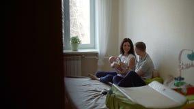 O homem e a mulher com o bebê em seus braços estão falando filme