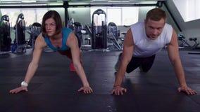 O homem e a mulher da aptidão empurram levantam no gym filme