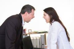 O homem e a mulher de negócio gritam cara a cara o perfil no escritório imagens de stock