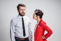 O homem e a mulher de negócio que opõem em um fundo cinzento Imagem de Stock Royalty Free