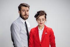 O homem e a mulher de negócio que opõem em um fundo cinzento Fotografia de Stock Royalty Free