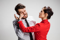 O homem e a mulher de negócio que opõem em um fundo cinzento Foto de Stock
