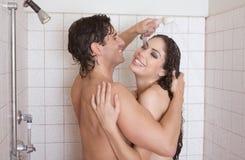 O homem e a mulher despidos no amor estão beijando no chuveiro Foto de Stock