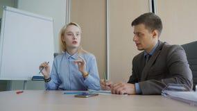 O homem e a mulher discutem trabalhar as edições, sentando-se no escritório moderno video estoque