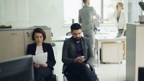 O homem e a mulher dos jovens estão esperando a entrevista de trabalho no escritório quando o gerente entrevistar um outro candid filme