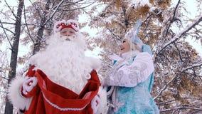 O homem e a mulher em trajes do ano novo na Noite de Natal estão felizes ver os presentes video estoque