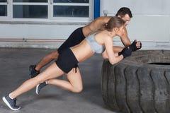 O homem e a mulher em um treinamento da aptidão do crossfit do pneu aquecem-se Fotos de Stock