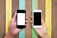 O homem e a mulher entregam guardar e usar o móbil, telefone celular, telefone esperto com tela isolada Fotos de Stock