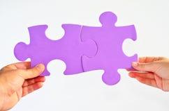 O homem e a mulher entregam o engodo diferente das partes do enigma de serra de vaivém das posses dois Foto de Stock Royalty Free