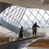 O homem e a mulher escalam a escadaria espiral no Louvre Paris Foto de Stock Royalty Free