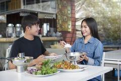 O homem e a mulher estão comendo o almoço Fotografia de Stock