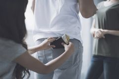 O homem e a mulher estão e falam, atrás do homem lá são uma menina que retire do bolso da parte traseira do homem uma bolsa Imagem de Stock
