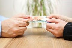 O homem e a mulher estão lutando sobre o dinheiro Imagem de Stock Royalty Free