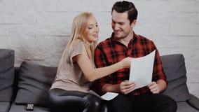 O homem e a mulher estão no sofá e na vista através dos originais vídeos de arquivo