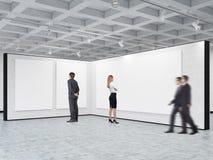 O homem e a mulher estão olhando cartazes vazios em uma galeria Fotografia de Stock