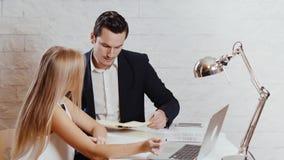 O homem e a mulher estão olhando o computador no escritório filme