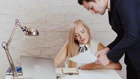 O homem e a mulher estão revendo originais no escritório vídeos de arquivo