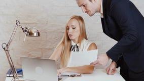 O homem e a mulher estão revendo originais no escritório video estoque