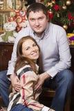 O homem e a mulher estão sentando-se perto da árvore de Natal Fotografia de Stock Royalty Free