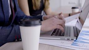 O homem e a mulher estão trabalhando na tabela com o portátil na empresa da agência corretora filme