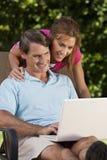 O homem e a mulher felizes acoplam-se usando o computador portátil Imagens de Stock Royalty Free