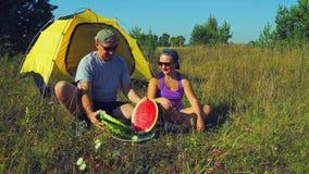 O homem e a mulher felizes perto de uma barraca no homem da floresta A cortam uma melancia com uma faca vídeos de arquivo