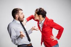 O homem e a mulher irritados de negócio que opõem em um fundo cinzento Fotografia de Stock