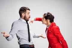 O homem e a mulher irritados de negócio que opõem em um fundo cinzento Foto de Stock Royalty Free
