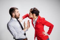 O homem e a mulher irritados de negócio que opõem em um fundo cinzento Fotos de Stock Royalty Free