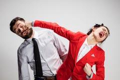 O homem e a mulher irritados de negócio que opõem em um fundo cinzento Fotos de Stock