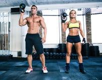 O homem e a mulher musculares do ajuste malham com bola da chaleira Foto de Stock Royalty Free