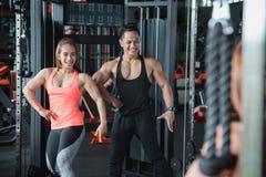 O homem e a mulher musculares dos pares levantam na frente do espelho Imagem de Stock Royalty Free