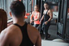 O homem e a mulher musculares levantam na frente do espelho Imagem de Stock Royalty Free