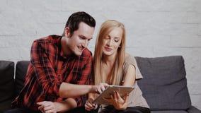 O homem e a mulher no sofá e estão guardando uma tabuleta filme