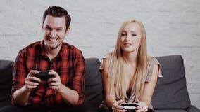 O homem e a mulher no sofá e estão jogando um jogo video estoque