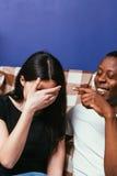 O homem e a mulher no sofá riem para fora gracejos altos, engraçados Imagens de Stock