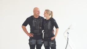 O homem e a mulher no terno muscular elétrico são dar certo, olhando a câmera video estoque