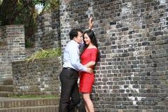 O homem e a mulher no vestido vermelho estão na parede de Ming Dynasty fotografia de stock royalty free