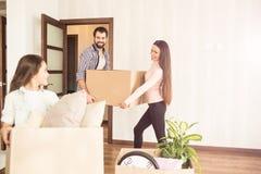 O homem e a mulher novos e bonitos estão guardando uma caixa do material e estão olhando a sua criança quando a menina pequena gu foto de stock