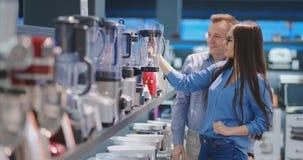 O homem e a mulher novos dos pares na loja de dispositivos selecionam um misturador para sua culinária vídeos de arquivo