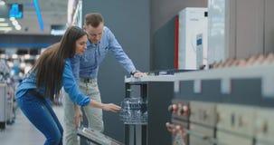 O homem e a mulher para abrir a porta de dispositivos da máquina de lavar louça na loja e a compará-los com outros modelos para c filme