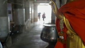 O homem e a mulher passam pela estátua budista, caminhada dos viajantes dos povos perto do símbolo dourado da fé dentro, pares no vídeos de arquivo