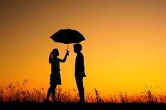 O homem e a mulher prendem o guarda-chuva no por do sol da noite Imagens de Stock
