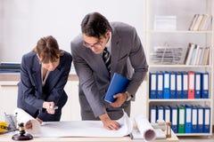 O homem e a mulher que discutem o projeto de construção fotos de stock