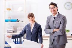 O homem e a mulher que discutem o projeto de construção foto de stock